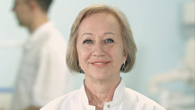 Medico femminile senior sorridente che esamina macchina fotografica Fotografia Stock