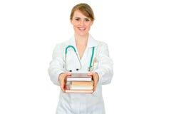 Medico femminile sorridente che dà parecchi libri Immagine Stock
