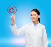 Medico femminile sorridente che indica il segno dell'ospedale Fotografie Stock