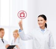 Medico femminile sorridente che indica il segno dell'ospedale Immagine Stock Libera da Diritti