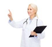 Medico femminile sorridente che indica qualcosa Fotografia Stock