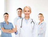 Medico femminile sorridente che mostra i pollici su Fotografia Stock Libera da Diritti