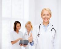 Medico femminile sorridente che mostra i pollici su Fotografia Stock