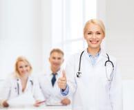Medico femminile sorridente che mostra i pollici su Immagini Stock Libere da Diritti