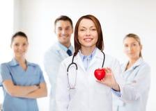 Medico femminile sorridente con cuore e lo stetoscopio Fotografia Stock Libera da Diritti
