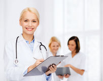 Medico femminile sorridente con la lavagna per appunti Fotografie Stock