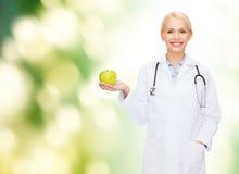 Medico femminile sorridente con la mela verde Fotografie Stock Libere da Diritti