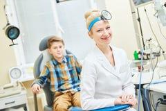 Medico femminile sorridente o l'orecchio OTORINOLARINGOIATRICO fiuta la gola con il paziente del ragazzo in clinica immagini stock