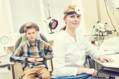 Medico femminile sorridente o l'orecchio OTORINOLARINGOIATRICO fiuta la gola con il paziente del ragazzo in clinica immagine stock libera da diritti