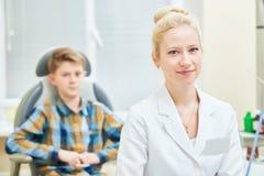 Medico femminile sorridente o l'orecchio OTORINOLARINGOIATRICO fiuta la gola con il paziente del ragazzo in clinica fotografia stock