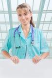 Medico femminile sorridente a trentadue denti di Beautyful con il cartello bianco Fotografia Stock