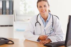Medico femminile sveglio che propone con i vetri Immagini Stock