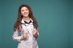 Medico femminile in uniforme professionale bianca con lo stetoscopio sul suo collo su fondo verde blu Copi lo spazio fotografia stock libera da diritti