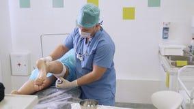 Medico in gamba di fasciature sterile dei vestiti del paziente dopo chirurgia per rimuovere le vene varicose video d archivio