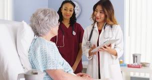 Medico giapponese ed infermiere nero che parlano con paziente anziano della donna nel letto di ospedale immagini stock libere da diritti