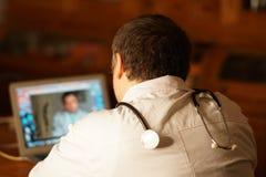 Medico girato parte posteriore che si siede al suo computer portatile immagini stock libere da diritti
