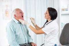 Medico guarda nella gola un uomo più anziano immagine stock libera da diritti