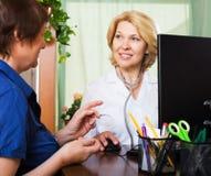 Medico invecchiato che ha notizie positive per una persona Fotografia Stock