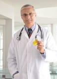 medico invecchiato della bottiglia che tiene prescrizione centrale Fotografie Stock