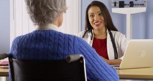 Medico ispano che divide buone notizie con il paziente Fotografia Stock