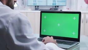 Medico lavora al computer portatile con lo schermo verde archivi video