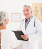 Medico maggiore che comunica con il suo paziente ammalato Fotografie Stock Libere da Diritti