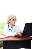 Medico maggiore occupato della donna in ufficio Immagini Stock
