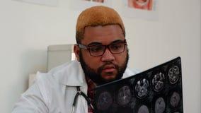 Medico maschio afroamericano che esamina immagine dei raggi x di tomografia computerizzata del cervello archivi video