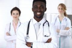 Medico maschio afroamericano felice con il personale medico all'ospedale Fotografie Stock Libere da Diritti