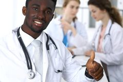 Medico maschio afroamericano sorridente felice che parla con il collega mentre sedendosi alla tavola Immagini Stock Libere da Diritti