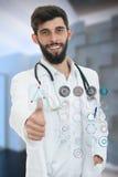 Medico maschio amichevole che mostra i pollici su nell'ospedale Immagine Stock Libera da Diritti
