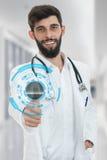 Medico maschio amichevole con la barba che mostra i pollici su Fotografia Stock