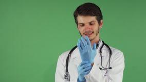 Medico maschio barbuto bello che indossa i guanti di gomma medici fotografia stock libera da diritti