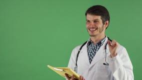 Medico maschio bello che ha un'idea mentre esaminando i documenti immagini stock libere da diritti