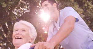 Medico maschio che assiste donna senior sulla sedia a rotelle nel cortile archivi video