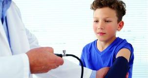 Medico maschio che controlla pressione sanguigna del paziente archivi video