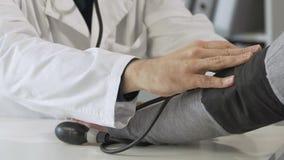 Medico maschio che controlla pressione sanguigna femminile dei pazienti all'esame, clinica archivi video