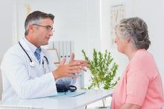 Medico maschio che conversa con il paziente femminile alla tavola immagine stock libera da diritti