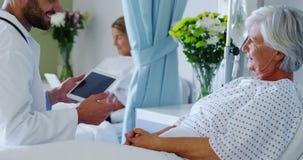 Medico maschio che discute perizia medica con la donna senior sulla compressa digitale stock footage