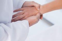Medico maschio che esamina una mano dei pazienti Fotografia Stock