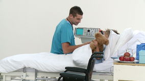 Medico maschio che gioca con un paziente ed il suo orsacchiotto video d archivio