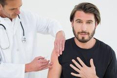 Medico maschio che inietta un braccio maschio dei pazienti dei giovani Fotografie Stock