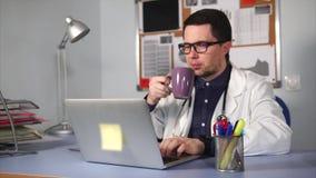 Medico maschio che lavora al suo workplacean ed ha una rottura per bere un certo caffè stock footage
