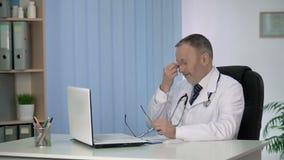 Medico maschio che osserva le cartelle sanitarie dei pazienti, stanche dopo il giorno lavorativo duro video d archivio