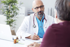 Medico maschio che parla con paziente Fotografie Stock Libere da Diritti