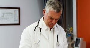 Medico maschio che per mezzo della compressa digitale mentre misurando altezza della ragazza video d archivio
