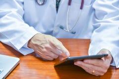 Medico maschio che per mezzo della compressa e del computer portatile durante la conferenza, salute Fotografia Stock Libera da Diritti