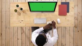 Medico maschio che posa le note dal suo computer Visualizzazione bianca video d archivio