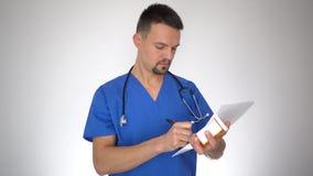 Medico maschio che scrive prescrizione al paziente video d archivio