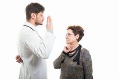Medico maschio ed il giuramento falso di mostra paziente senior femminile gesture immagini stock